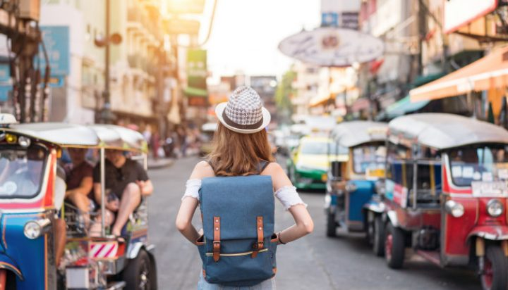 The back of a young woman walking and walking along the pedestrian street in the evening in Bangkok, Thailand, travelers and tourists. (The back of a young woman walking and walking along the pedestrian street in the evening in Bangkok, Thailand, trav